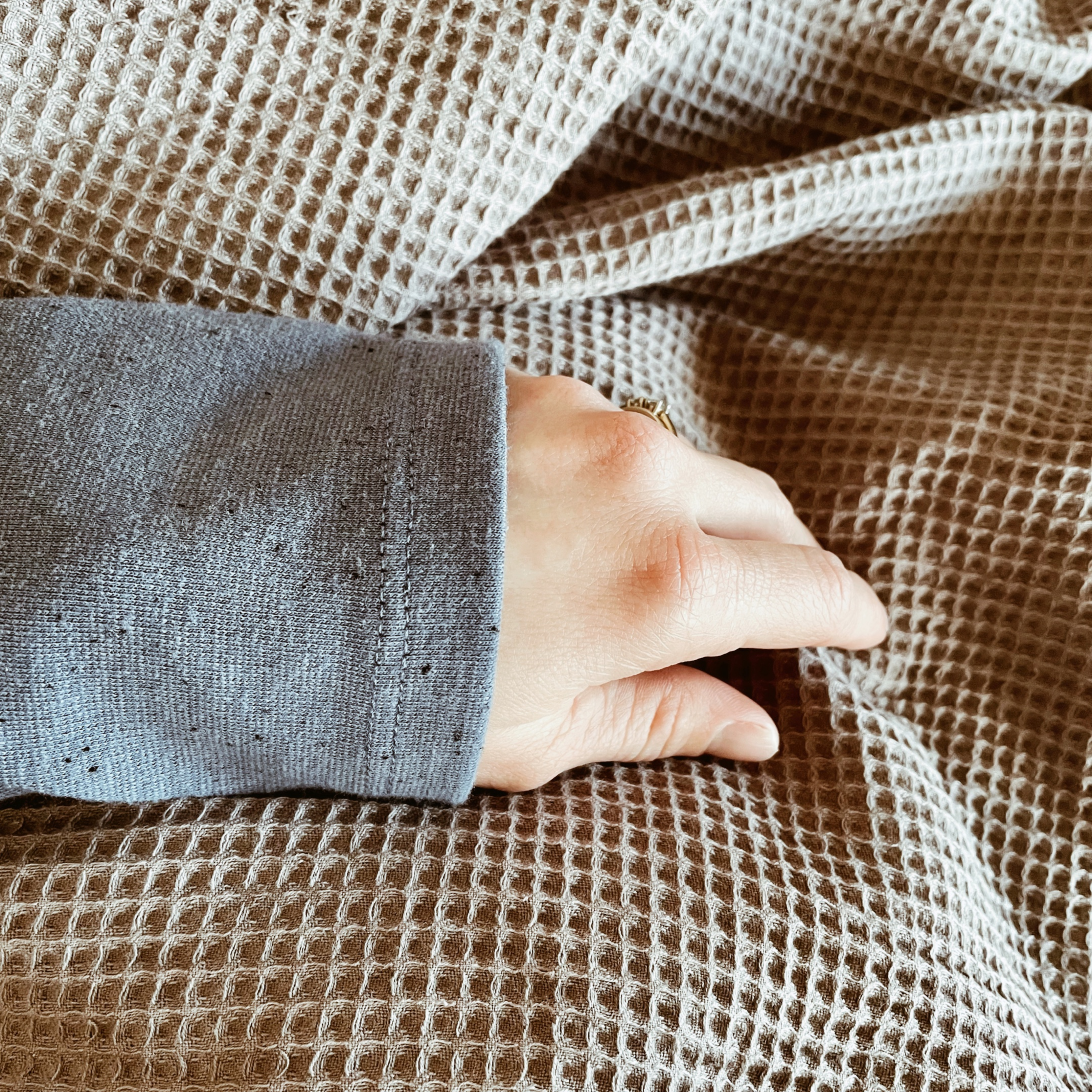 Woman's arm on top of a grey waffle duvet cover.
