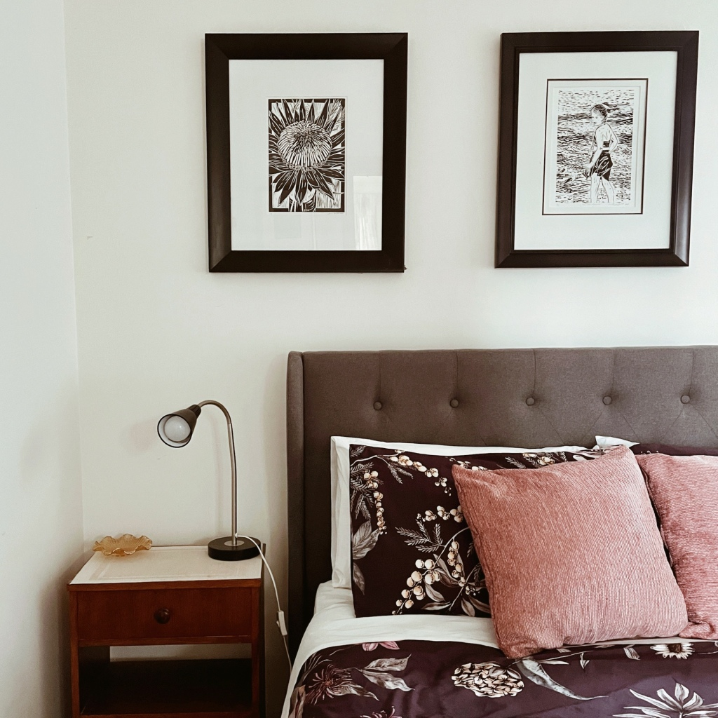 Bed and bedside table below two framed black and white line drawings.