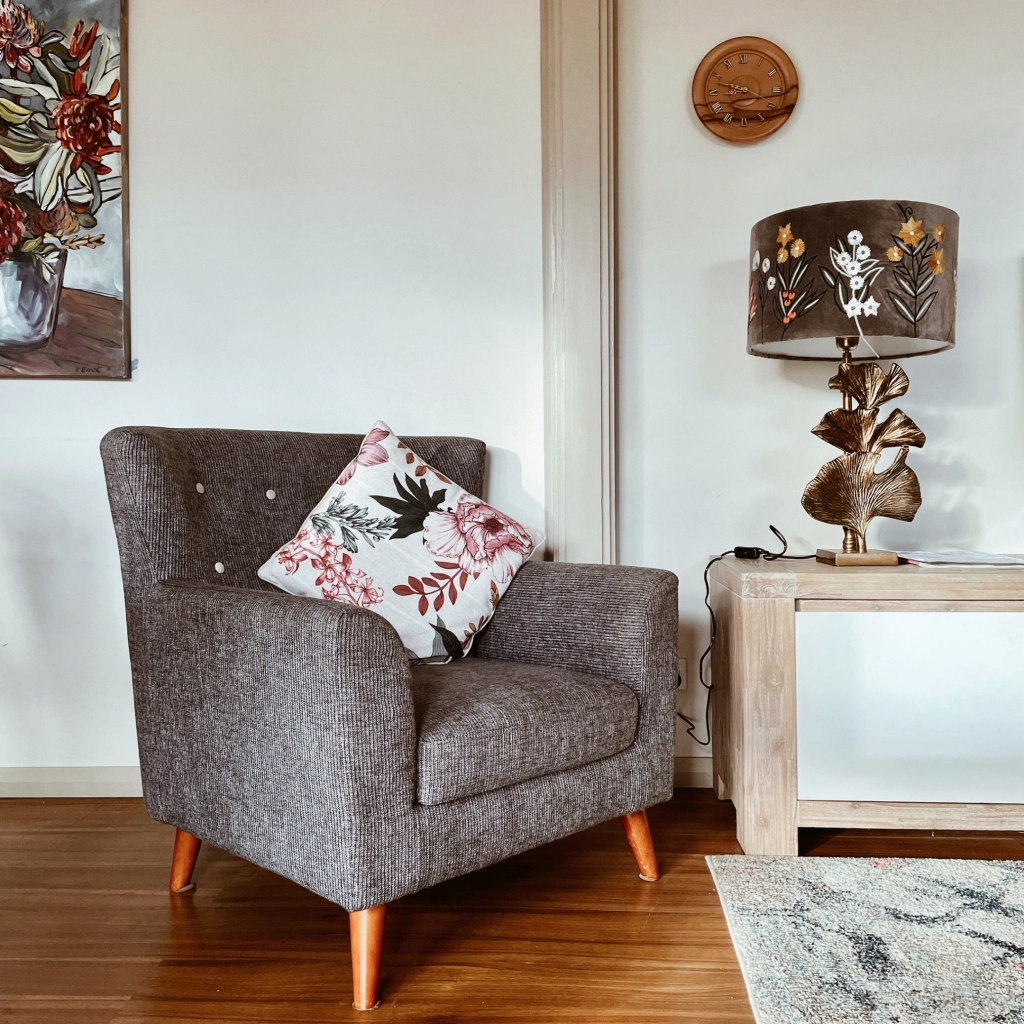 Grey armchair beside a long tv-unit with decorative lamp.