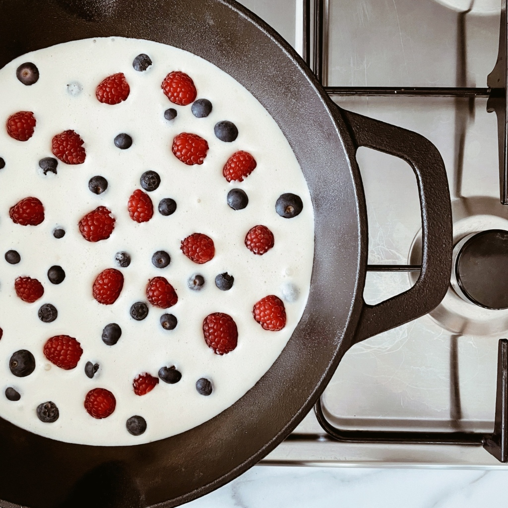 Looking down at clafoutis mixture in a cast iron skillet, dotted with blueberries and raspberries.