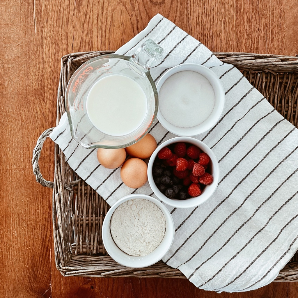Looking down on a wicker tray lined with a black and white stripe tea towel, containing a jug of milk, ramekins on flour and sugar, eggs and a ramekin of berries.