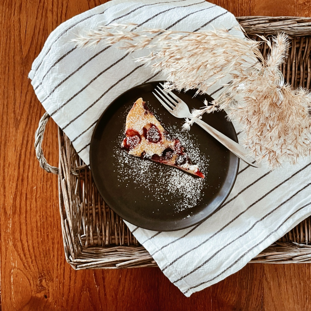 Berry clafoutis on a black plate sitting on a black and white striped teatowel in a wicker tray. A vase of dried grasses is beside.