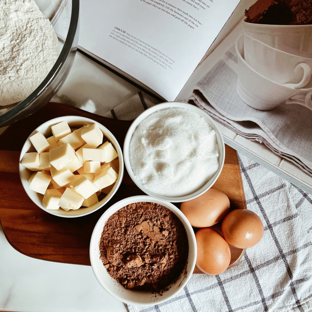 Flour, butter, sugar, cocoa and eggs portioned out beside an open cookbook.