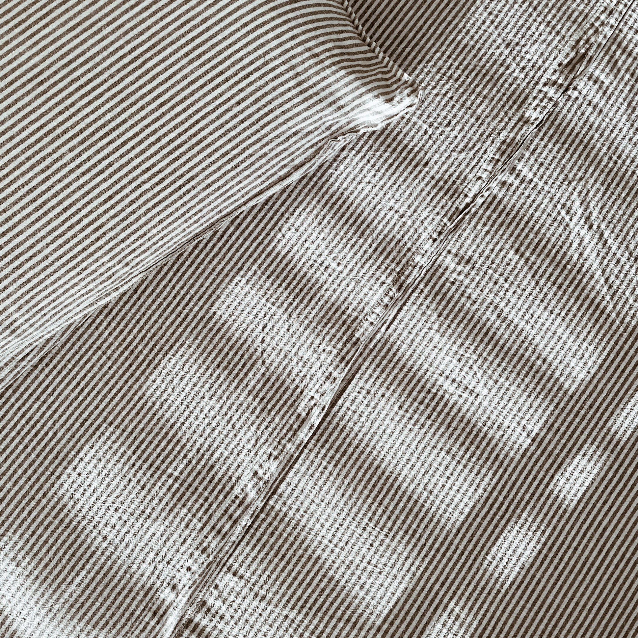 Looking down on a bed made up with grey and white striped linen sheets.