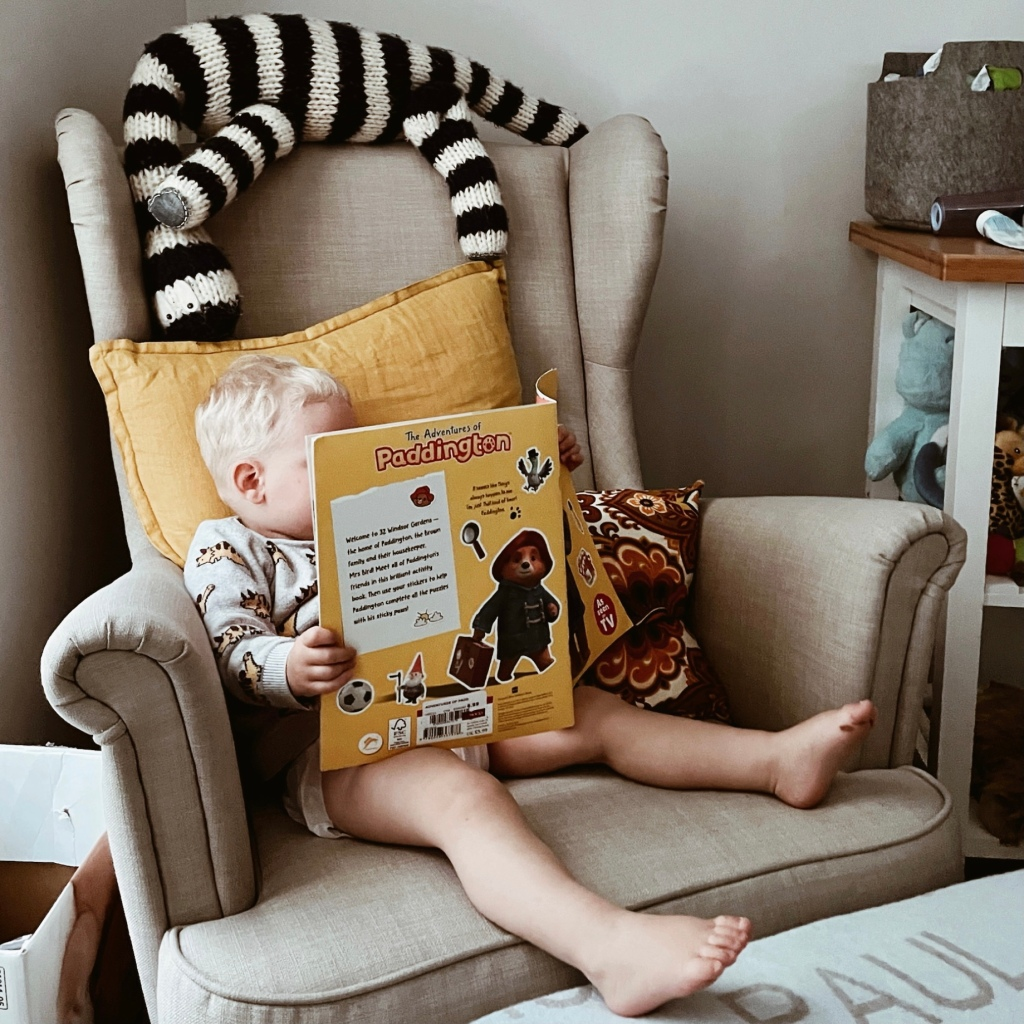 Toddler sitting on an armchair reading a book.