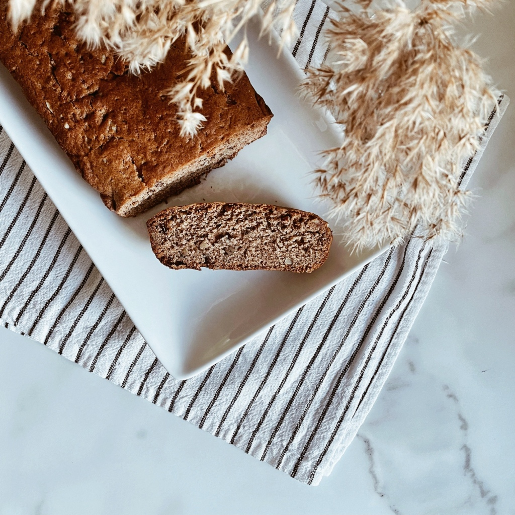 Slice of banana bread off a loaf, sitting a rectangular plate atop a striped tea towel near a vase of dried grasses.