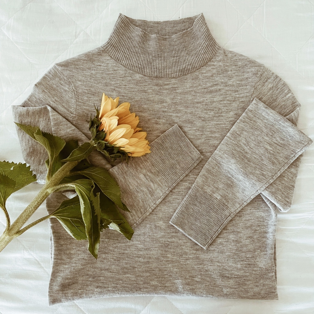 Flat lay of a grey mockneck jumper with a yellow sunflower.